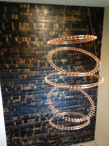 Holzgetäfelte Wand und Lampenspiel im Treppenaufgang
